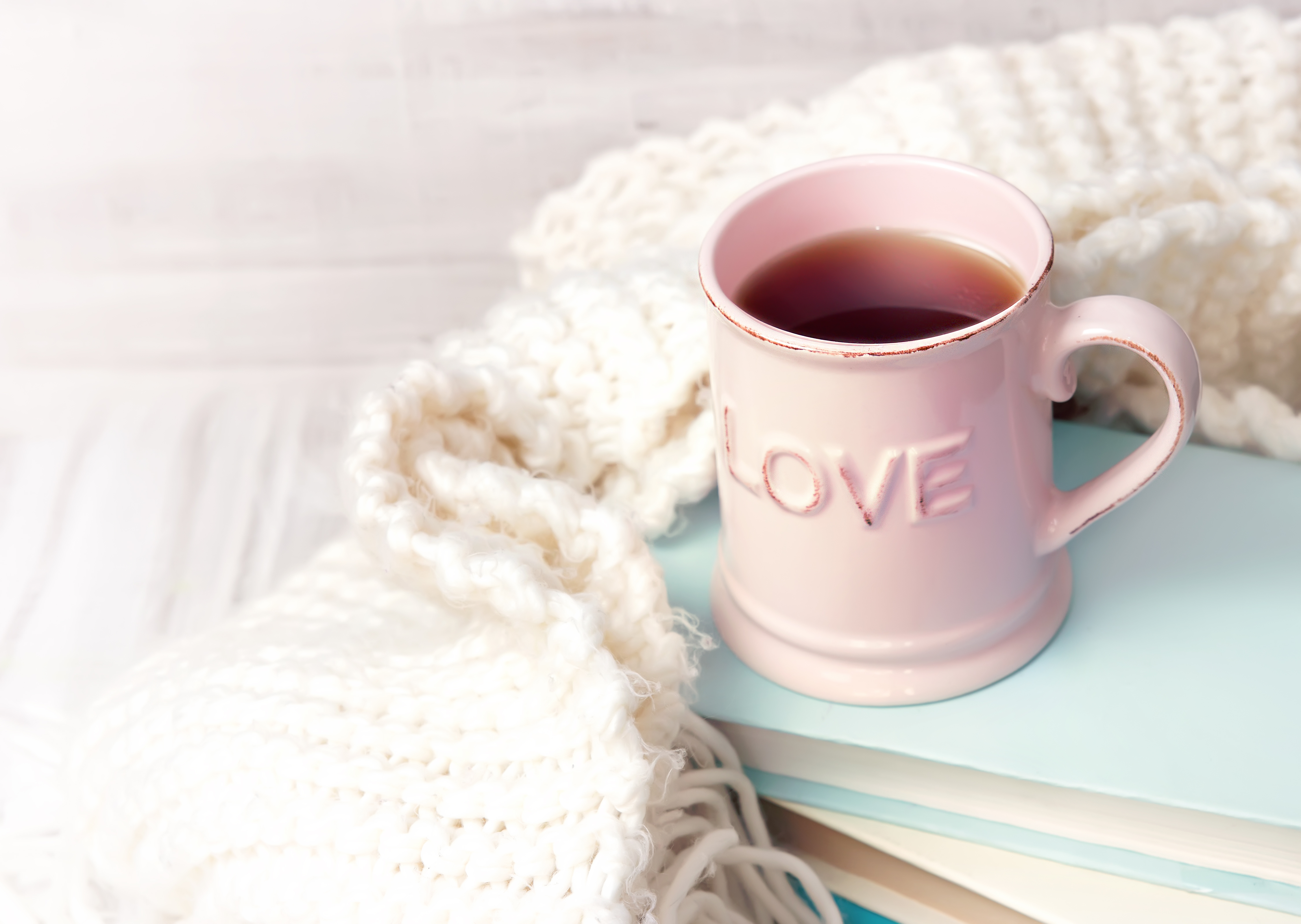 Pink coffee tea mug on stack of books with knits vintage background empty space for text. Valentine's day holiday icon. Retro  literature concept.
